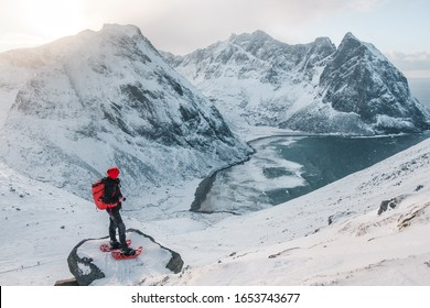 Famous view over Kvalvika beach from Ryten mountain in winter. On e of the biggest tourist attractions in lofoten islands. very popular hike in norway. Girl sitting on the edge watching over the beach