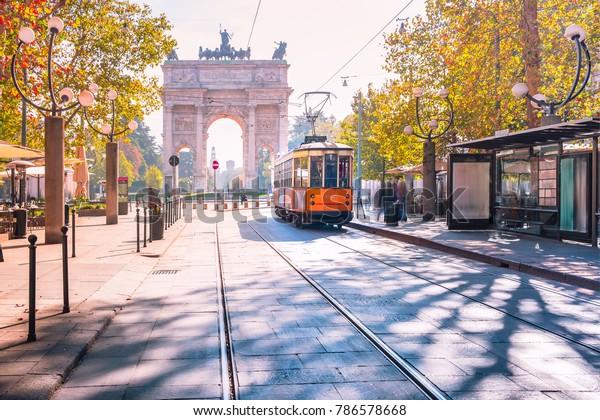 Berühmte Vintage-Tram im Zentrum der Altstadt von Mailand an sonnigen Tagen, Lombardei, Italien. Friedensbogen oder Arco della Pace auf dem Hintergrund.