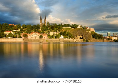 Famous Vysehrad church during sunny day. Amazing cloudy sky in motion. Hot summer season. Typical landscape reflection at Vltava river, Prague, Czech republic