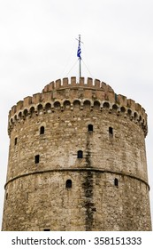 the famous White Tower by the harbour of thessaloniki Greece waving its Greek flag on top .