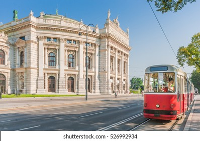 Famous Wiener Ringstrasse with historic Burgtheater (Imperial Court Theatre) and traditional red electric tram at sunset with retro vintage Instagram style filter effect in Vienna, Austria