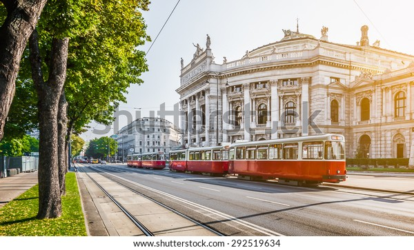 Famous Wiener Ringstrasse with historic Burgtheater (Imperial Court Theatre) and traditional red electric tram at sunrise with retro vintage Instagram style filter effect in Vienna, Austria