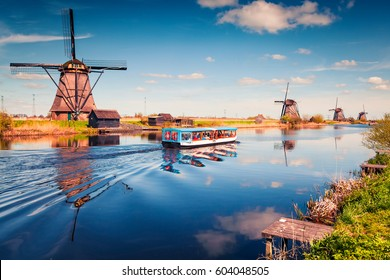 Famous windmills in Kinderdijk museum in Holland. Sunny spring morning in countryside. Colorful outdoor scene in Netherlands, Europe. UNESCO World Heritage Site. Artistic style post processed photo.