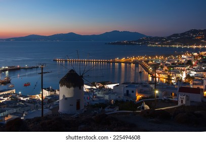 Famous windmills of Mykonos on the background of the night in the lights of the town.