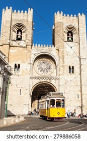 Famous yellow 28 tramway  of Lisbon passing in front of Santa Maria cathedral in Portugal