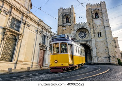 A famous yellow tram 28 passing in front of Santa Maria cathedral in Lisbon, Portugal