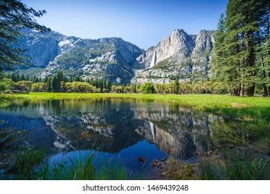 Famous Yosemite park view to waterfall and valley. Water mirroring in front of mountains and green fresh grass.
