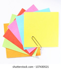 A fan of colorful post-it notes with paperclip, white background