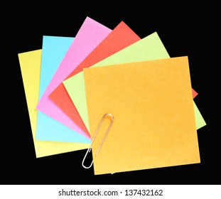 A fan of colorful post-it notes with paperclip, black background