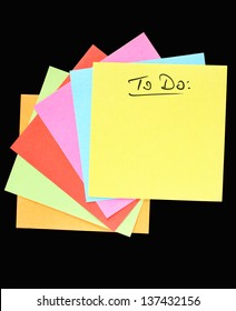 """A fan of colorful post-it notes, """"To do"""" lettering, black background"""