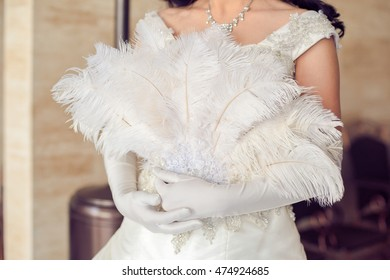 Fan feather in hands of the bride Wedding concept