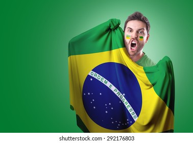 Fan holding the flag of Brazil on green background
