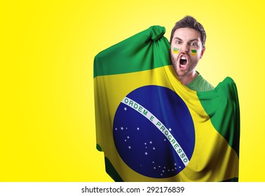 Fan holding the flag of Brazil on yellow background