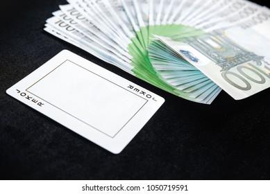 Fan of one hundred euro banknotes money on casino poker with jocker card on black background