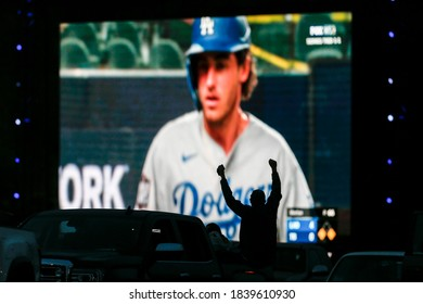 A fan reacts during a drive-in live broadcast of game 3 of the World Series between the Tampa Bay Rays and the Los Angeles Dodgers in the parking lot of Dodger Stadium in Los Angeles, Oct. 23, 2020.