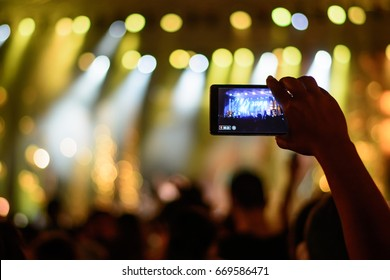 Fan recording concert with mobile phone
