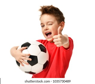 Fan sport boy player hold soccer ball in red t-shirt celebrating happy smiling laughing show thumbs up success sign free text copy space isolated on white background