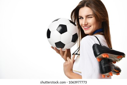 Fan sport woman player in red uniform hold soccer ball and boots celebrating winking on white background