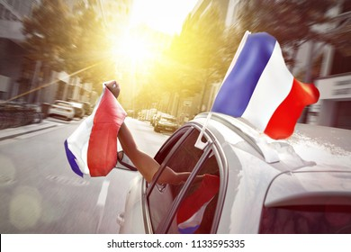 Fan waving a French flag out of a car window