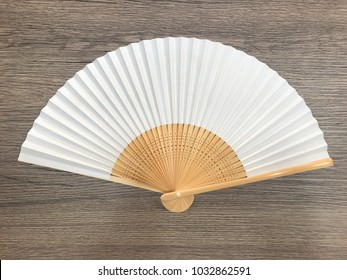 Fan White Chinese or Japanese made of bamboo and paper. Placed on an old wooden board. And space for text or symbol