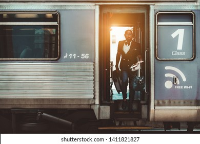 A fancy bald bearded African businessman in glasses and with travel bags in his hands is leaving the first-class train car and descends the stairs to the platform after finishing his business trip