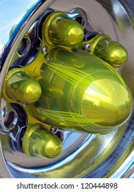 Fancy bolt covers on chrome hub of restored antique automobile