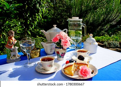 Fancy breakfast outdoors served on the blue tablecloth with pink flowers, black tea and berries cakes. Teatime.