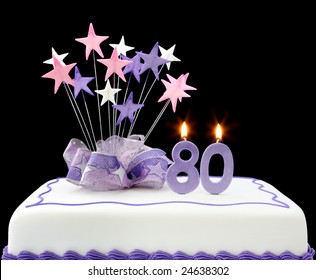 Fancy cake with number 80 candles.  Decorated with ribbons and star-shapes, in pastel tones over black background.