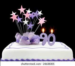 Fancy cake with number 90 candles.  Decorated with ribbon and star-shapes, in pastel tones on black background.