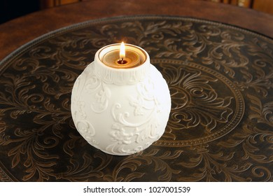 Fancy candle holder with lit flame on table.