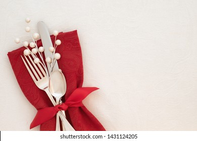 Fancy Christmas Table Place Setting with red napkin, silverware, and white berries on creamy white tablecloth background with copy space.