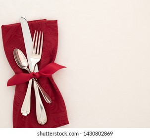 Fancy Christmas or Valentines Day Table Place Setting with cloth red napkin, silverware, and bow on creamy white tablecloth background with copy space.