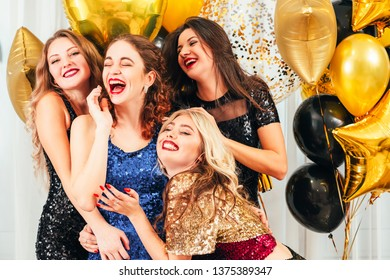 Fancy cocktail party. Girls enjoying entertainment, laughing, having fun, looking amused in hall decorated with golden balloons.