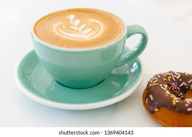 Fancy coffee, latte art, espresso, cappuccino in an aqua cup with a chocolate glazed donut on a white background