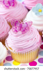 Fancy cupcakes, in pastel tones.  Delicious sweet treats.