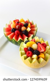 Fancy cut melon and watermelon with assorted fruit inside inicluding strawberries, raspberries, grapes, canteloupe, pineapple, and sliced peaches