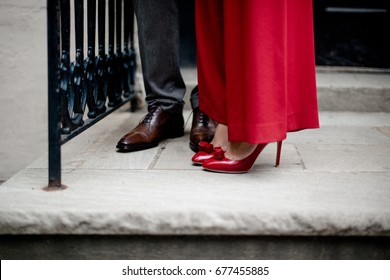 Fancy dressed up couple at door steps, Brown leather shoes and red high heels