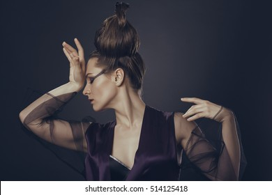 Fancy female fashion model with her right hand on forehead having a headache against dark background. Fashion stress. Drama queen.