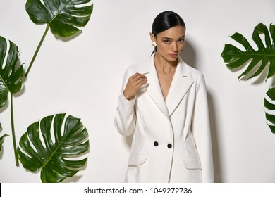 Fancy girl is posing in a studio on a background of a white wall with big green leaves. She wears a white pantsuit. Woman looks into a camera. Closeup. Horizontal.