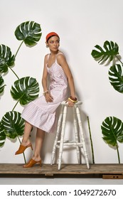 Fancy girl sits on a white stool on a wooden platform in a studio on a background of a white wall with big green leaves. She wears a striped pink dress, red headband, bracelets and brown mule shoes.