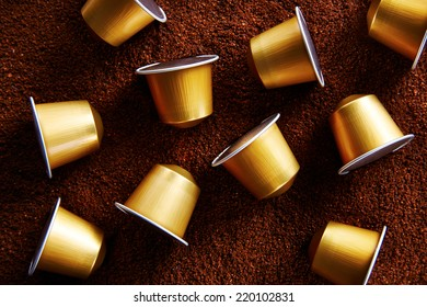 Fancy gold coffee capsules on coffee background
