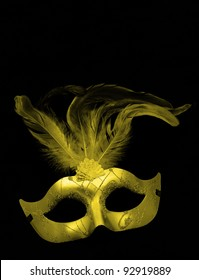 Fancy Gold / Yellow Feathered Mask isolated on a black velvet background