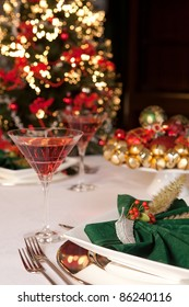 Fancy green napkins and baubles in front of a blurred christmas tree