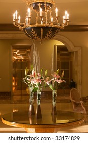 Fancy hotel lobby with chandelier and flowers.