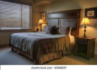 Fancy hotel room highlighted by a shutters covered window and two night table lamps.