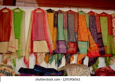 Fancy Indian silk suits hanging on display in a Swadeshi khadi handloom exhibition at Dilli Haat, New Delhi, India