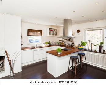 fancy kitchen with dark wooden floor and white cupboards