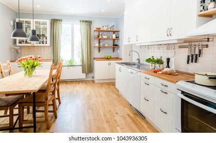 fancy kitchen interior kitchen table with tulips, green curtains and white cupboards