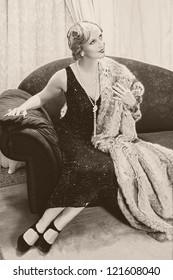 Fancy lady in 1920s style sitting on a luxury chaise-longue - noise has been added for vintage effect