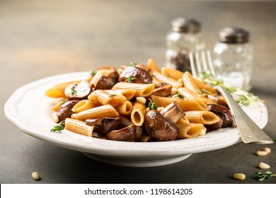 Fancy organic whole grain penne pasta with champignons, pine nuts and thyme. Healthy italian food concept.